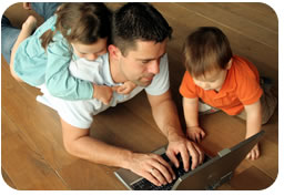 Picture of a father with his daughter on his back and his son by his side, while he is typing on his laptop computer.